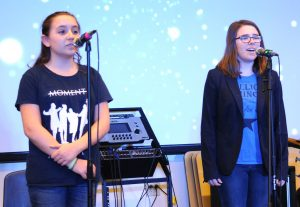 Middle schooler and older sister performing.