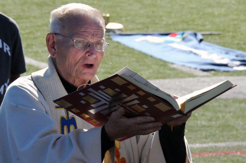 Fr. John preaching outdoors with a bible